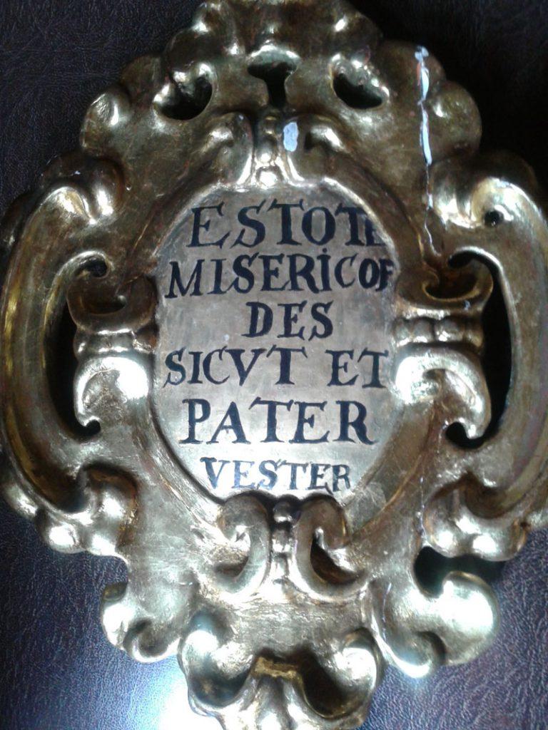 """Laska wizytatorska Arcybractwa Miłosierdzia. Rewers głowicy z napisem """"Bądźcie miłosierni jako Ojciec wasz""""."""